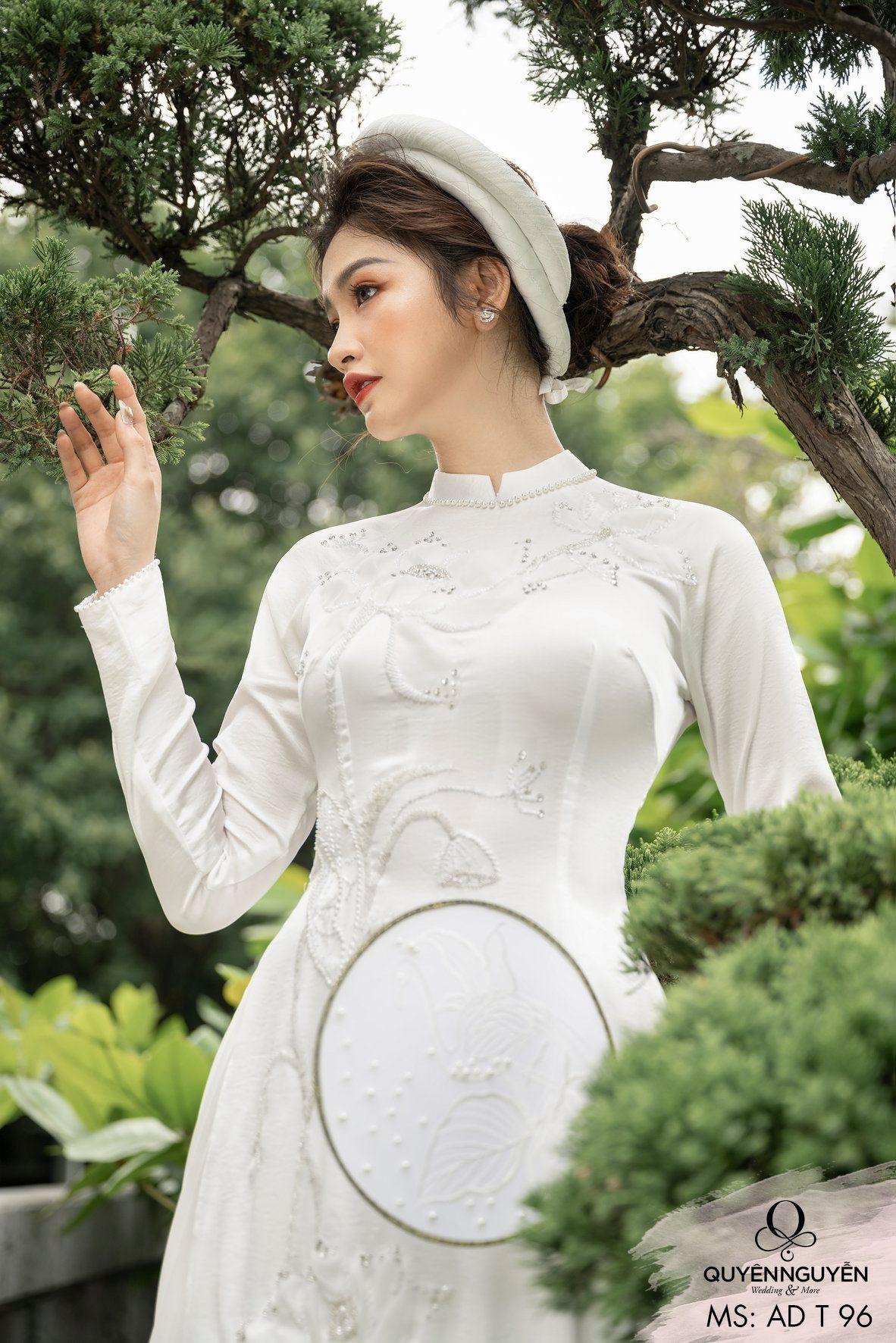 Áo dài màu trắng với hoạ tiết bông hoa sen đính hạt lấp lánh xung quanh