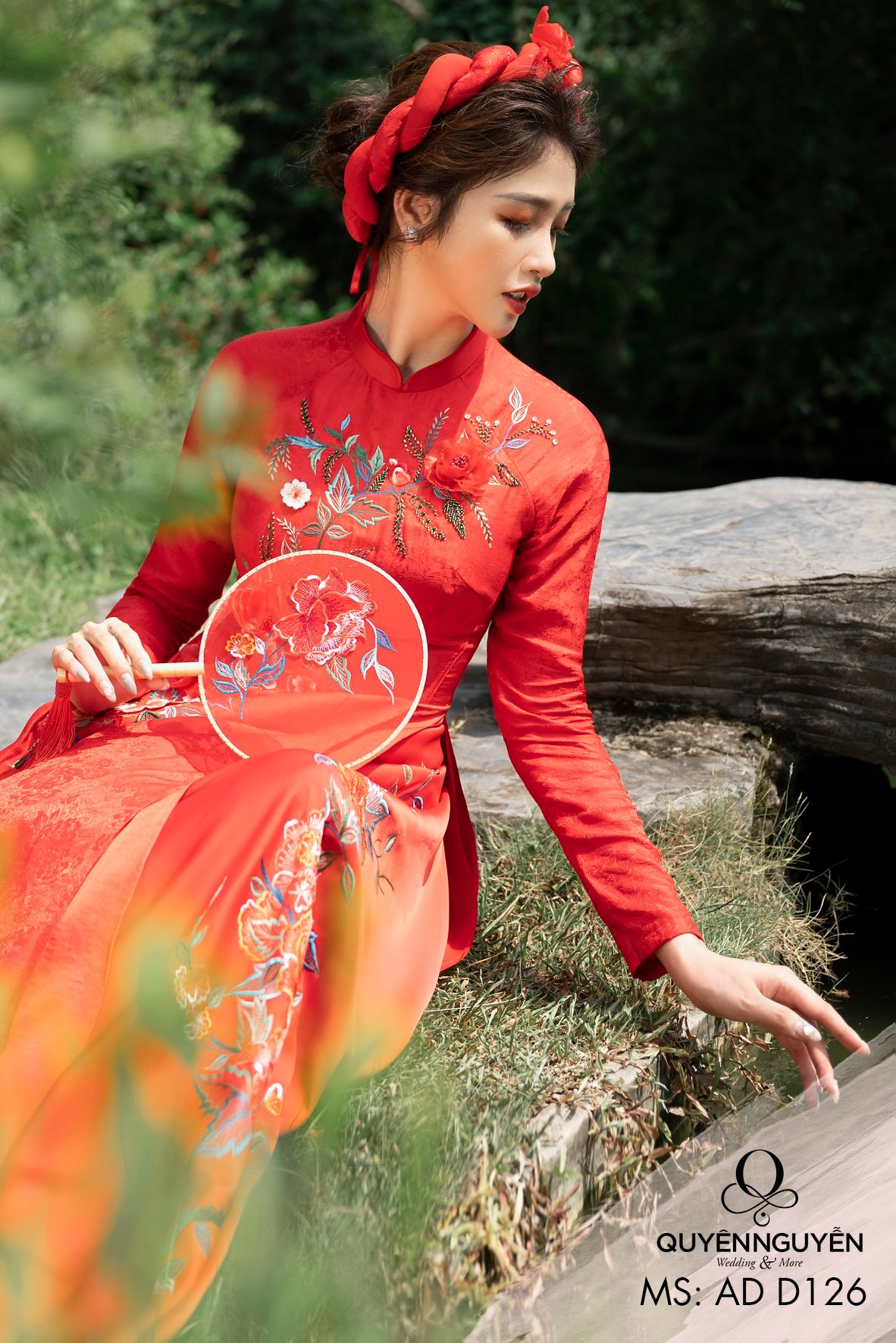 Áo dài màu đỏ với bông hoa được đính nổi bật bên ngực trái